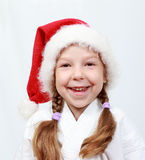 The little girl of four years with a cap on his head santa claus. The little girl with a cap on his head santa claus Royalty Free Stock Image