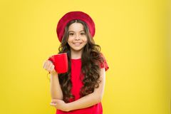 Little girl in french style hat. Tea time. happy girl with long curly hair in beret. beauty fashion. childhood. Hairdresser salon. parisian child on yellow royalty free stock photography