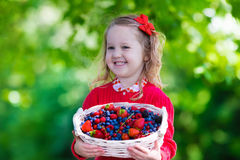 Little girl with fresh berries in a basket Royalty Free Stock Photos