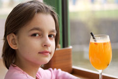Little girl with a fresh juice in a glass Royalty Free Stock Photo