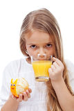 Little girl with fresh orange juice holding snail made of orange Royalty Free Stock Images