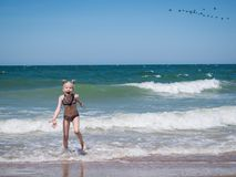 A little girl in fright from the raging sea. The girl runs away in fear from the raging sea. The wind carries to the sea an inflatable mattress, the girl runs Royalty Free Stock Photos