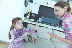 The little girl is frightened and protected from babysitting. She curses the girl and threatens her with a finger. The girl is standing next to a large window Stock Images