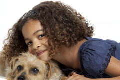Little girl with frizzy hair hugging dog. Young girl with frizzy hair is hugging a little dog on a white background royalty free stock photo