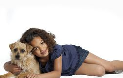Little girl with frizzy hair hugging dog Royalty Free Stock Photos