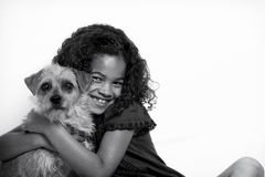 Little girl with frizzy hair hugging dog Stock Images