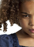 Little girl with frizzy hair looking angry. Close up of the right part of the face of young girl with frizzy dark brown hair who is looking angry stock photography