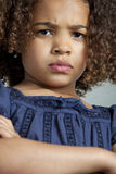 Little girl with frizzy hair looking angry. Close up of the face of young girl with frizzy dark brown hair who is looking angry, looking down in the camera with stock image