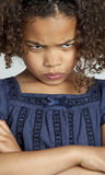 Little girl with frizzy hair looking angry. Close up of the face of young girl with frizzy dark brown hair who is looking angry, looking down in the camera with royalty free stock image