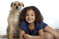 Little girl with frizzy hair together with her dog. Young girl with frizzy hair is posing together with a little dog on a white background stock image