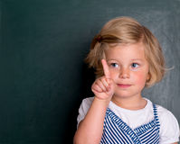 Little girl in front of black board with forefinger up Stock Photography
