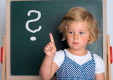 Little girl in front of black board with forefinger up Royalty Free Stock Photography