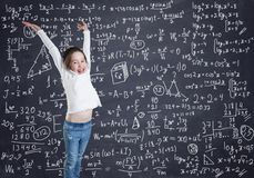 A little girl in front of the blackboard with formulas and calculations royalty free stock photography