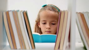 Little girl in front of bookshelf stock footage