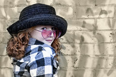 Little girl in front of brick wall Stock Images