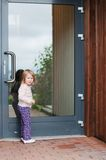 Little girl in front of the door. Little girl standing in front of the door stock images