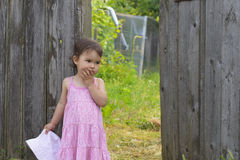 Little girl in front of the gate thinking at countryside Royalty Free Stock Images