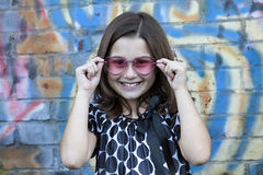 Little girl in front of graffiti wall Stock Images