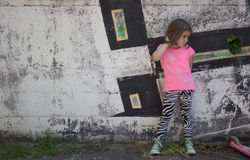 Little girl in front of graffiti wall Stock Photos