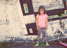 Little girl in front of graffiti wall Royalty Free Stock Images