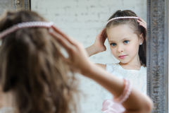 Little girl front the mirror. Playint to princess Royalty Free Stock Images