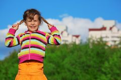 Little girl in front of trees and buildings Royalty Free Stock Images