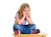 Little girl is sad. Little girl in front of white background is in bad mood royalty free stock image