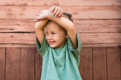 Little girl in front of a wooden wall Royalty Free Stock Image