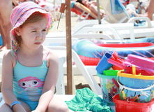 Little girl frowning sitting on the beach Royalty Free Stock Photography