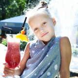Little girl with fruit cocktail Stock Image