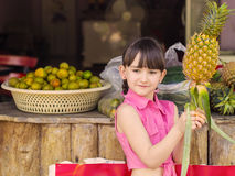 Little girl at fruits Royalty Free Stock Photos