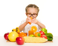 Little girl with fruits and vegetables make juice Royalty Free Stock Images