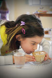 FULL TEA CUP. A cute little tween girl leaning forward, carefully sipping tea from a full tea cup in typical little girl fashion. Shallow depth of field Stock Images