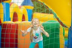 Beautiful little girl having fun peeking from behind the mesh inflatable trampoline. stock photos