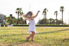 Little girl fun rides and jumps on the lawn Royalty Free Stock Photography