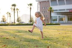 Little girl fun rides and jumps on the lawn Royalty Free Stock Photo