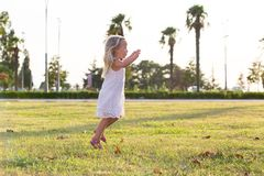 Little girl fun rides and jumps on the lawn Royalty Free Stock Image