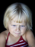 Little girl with funny angry face. A four year old girl looking angry and cross at the camera. Isolated on black Royalty Free Stock Photography