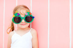 Little girl in funny Christmas glasses. Adorable little girl in a funny Christmas glasses over colorful Caribbean house background stock photos