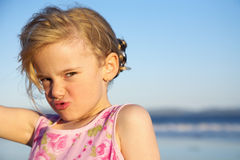 Little girl with funny face. Little girl making a funny expression at the beach stock image