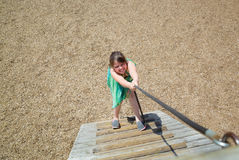 Little girl with funny face expressions playing, climbing up on a wooden stairs Stock Photos