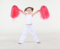 Little girl with funny hairdo holds in raised hands pompoms Royalty Free Stock Image
