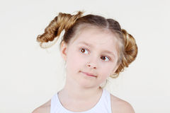 Little girl with funny hairdo looks into distance. Stock Images