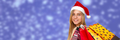 Little girl in fur-cap with shopping bags on blue background. Christmas. Little girl in fur-cap with shopping bags. Shopping over blue background. Christmas Royalty Free Stock Photos