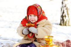 Little girl in a fur coat and red scarf Russian drinking tea on. A background of a samovar. Portrait of girl dressed in Russian style on a background of a Royalty Free Stock Image