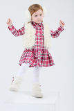 Little girl in fur headphones and vest dances Royalty Free Stock Photos