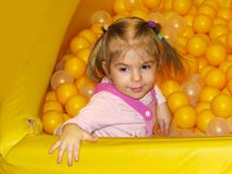 Little girl in the game room with balls. Little girl in the game room with yellow balls Royalty Free Stock Photo