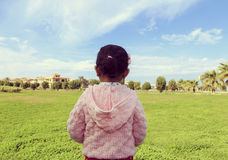A little girl in a garden with blue sky. Stock Images