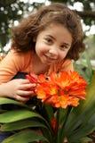 Little girl in a garden of clivia miniata stock images