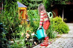 Little girl in a garden with green watering can Stock Image